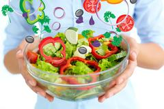 close-up of fresh vegetable salad in bowl held by female - stock photo
