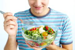 close-up of fresh vegetable salad being eaten by man - stock photo