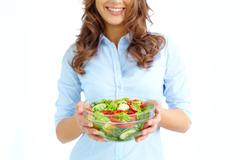 close-up of female holding bowl with fresh salad - stock photo