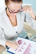 business lady with pen looking at document - stock photo