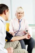 portrait of mature woman measuring blood pressure of her husband at home - stock photo