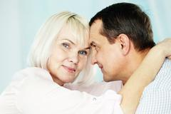 portrait of mature woman looking at camera while embracing her husband - stock photo