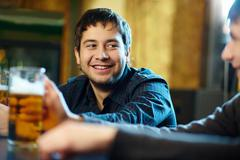 Happy man with glass of beer looking at his friend in pub Stock Photos