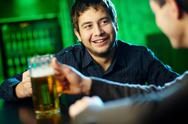 Stock Photo of two guys hanging out in bar with mugs of beer