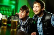 Stock Photo of two friends spending time at sport bar enthusiastic about the game