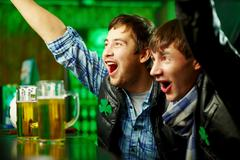 Happy men shouting while watching football match broadcast in pub Stock Photos