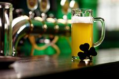 image of glass of beer with shamrock leaf on pub table - stock photo