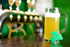 A glass of beer on a bar counter with a leaf of shamrock Stock Photos
