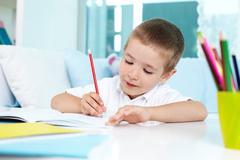 Lovely boy drawing with a pencil Stock Photos