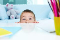 playful little boy hiding under the table - stock photo