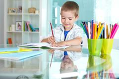Happy schoolkid drawing with multicolored pencils Stock Photos