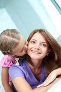 little cutie giving her mother a kiss on the cheek - stock photo