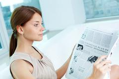Attractive business lady with a newspaper being absorbed in her thoughts Stock Photos