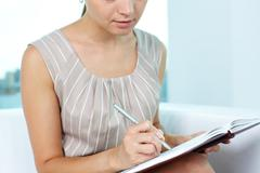 Attractive young woman taking notes in order not to forget something Stock Photos
