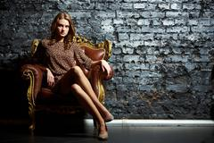 Gorgeous girl sitting in a vintage chair presenting the contrast of high fashion Stock Photos