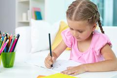 Cute little girl drawing with crayons Stock Photos