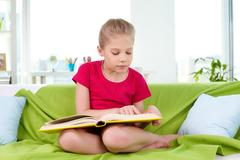 portrait of lovely girl reading big book at home - stock photo
