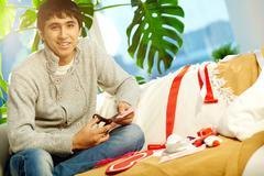 portrait of happy man making valentine red paper heart and looking at camera - stock photo