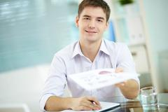 Portrait of young businessman giving document to colleague at meeting Stock Photos