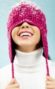 Portrait of playful woman in knitted winter cap smiling Stock Photos
