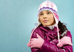 pretty woman in warm jacket and knitted cap is cold in winter - stock photo