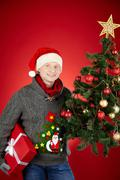 portrait of happy man in santa cap with giftbox and decorated xmas tree looking - stock photo