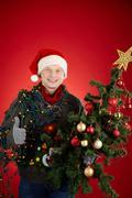 Portrait of happy man in santa cap decorated xmas tree showing thumb up Stock Photos
