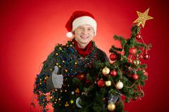 Portrait of happy man in santa cap decorated xmas tree showing thumb up Stock Photos