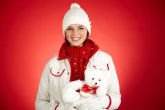 Portrait of happy girl in winterwear holding white teddy bear and looking at cam Stock Photos