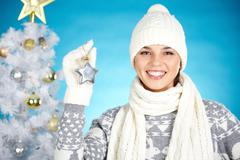 joyful girl with decorative toy star looking at camera with xmas tree behind - stock photo