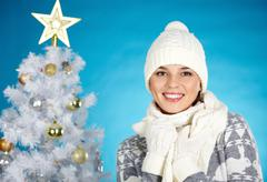 joyful girl in winterwear looking at camera with decorated firtree behind - stock photo