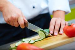 Image of male hand with knife cutting cucumbers on wooden board Stock Photos