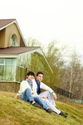 Tilt up of stylish homosexual lovers sitting on the grass in front of the townho Stock Photos