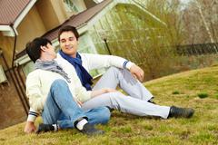 Tilt-up shot of young people looking at each other lovingly sitting on a grassy Stock Photos