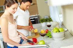 Tilt up of a sweet couple cooking together at home, girl cutting paprika while h Stock Photos
