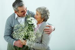 mature husband presenting his better half with white flowers, isolated on grey - stock photo