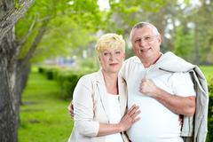 mature woman and her husband looking at camera while having rest outside - stock photo