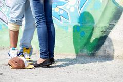 Image of young couple legs on background of graffiti wall Stock Photos