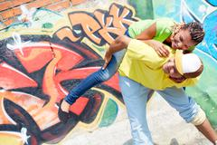 Image of young girl on her boyfriend's back on background of graffiti wall Stock Photos