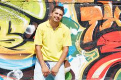 Image of young guy embracing his girlfriend on background of graffiti wall Stock Photos