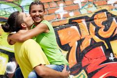 Image of young man holding his happy girlfriend on background of graffiti wall Stock Photos