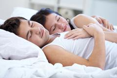 Lovers sleeping together in bed Stock Photos