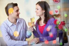 a young happy couple sitting in restaurant and drinking wine - stock photo