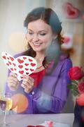 a young girl in restaurant holding valentine card - stock photo