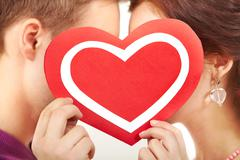 two young people kissing behind a paper heart - stock photo