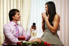 A young man giving engagement ring to his girlfriend while making her proposal Stock Photos