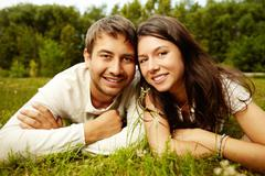 Close-up portrait of two happy lovers resting on the grass Stock Photos
