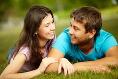Lovers lying on the grass and looking at each other with affection Stock Photos