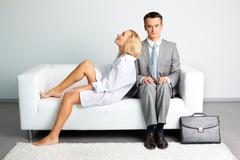 man in business suit feeling uncomfortable setting next to a pretty lady wearing - stock photo
