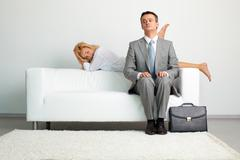 Playful sexy girl seducing the businessman who looks almost scared of her activi Stock Photos